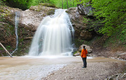 La ragazza sta vicino alla al bei ampi cascata e sguardo Immagini Stock