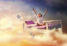 La ragazza sta volando nel suo letto fotografie stock libere da diritti