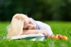 La ragazza stanca dorme sui libri che si trovano sull'erba Fotografia Stock