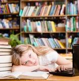 La ragazza stanca nella biblioteca insegna a prima degli esami Fotografia Stock