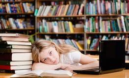 La ragazza stanca nella biblioteca insegna a prima degli esami Immagini Stock