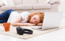 La ragazza stanca sta avendo un resto sul pavimento Immagine Stock