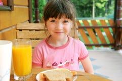La ragazza stupita del bambino ha una prima colazione all'aperto Immagini Stock Libere da Diritti