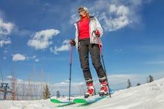 La ragazza su sci alpino sta su una pista nevosa contro il cielo Fotografie Stock Libere da Diritti