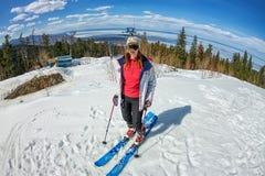 La ragazza su sci alpino sta su una pista nevosa contro il cielo Immagine Stock Libera da Diritti