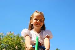 La ragazza su un'oscillazione su un fondo di cielo blu Fotografia Stock