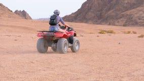La ragazza su una bici del quadrato guida attraverso il deserto dell'Egitto video d archivio