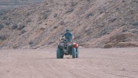 La ragazza su una bici del quadrato guida attraverso il deserto dell'Egitto archivi video