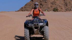 La ragazza su una bici del quadrato guida attraverso il deserto dell'Egitto su fondo delle montagne stock footage