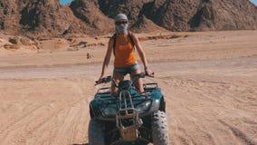 La ragazza su una bici del quadrato guida attraverso il deserto dell'Egitto su fondo delle montagne archivi video