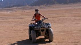 La ragazza su una bici del quadrato guida attraverso il deserto dell'Egitto su fondo delle montagne video d archivio