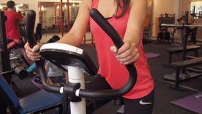 La ragazza su una bicicletta in una palestra La bella ragazza in maglietta rossa pedals nel simulatore video d archivio