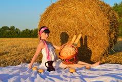 La ragazza su una falciatura con un canestro di pane e di una brocca di latte Fotografia Stock