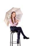 La ragazza su una sedia con un ombrello Fotografie Stock Libere da Diritti