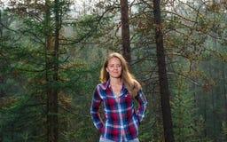 La ragazza sui precedenti degli alberi Fotografia Stock