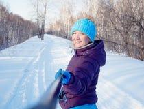 La ragazza sui precedenti di una foresta dell'inverno fa il Se della foto immagini stock