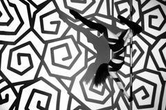 La ragazza sul pilone fa l'esercizio contro lo sfondo dei modelli neri Fotografia Stock Libera da Diritti