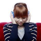 La ragazza sul sofà rosso ascolta grande musica Immagini Stock