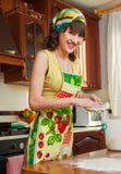 La ragazza sulla cucina Immagini Stock
