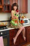 La ragazza sulla cucina Fotografie Stock