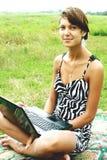 La ragazza sulla natura di una cassa del computer portatile Fotografia Stock