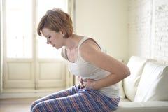 La ragazza sulla tenuta dello strato del sofà che danneggia il crampo di stomaco di sofferenza della pancia ed il periodo fanno s Fotografie Stock Libere da Diritti