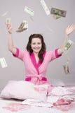 La ragazza sulle banconote di caduta del letto Fotografia Stock