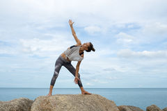 La ragazza sulle pietre che occupano con l'yoga, uno scolo nel Asana, yoga al mare, su un cavallino di bello paesaggio immagini stock