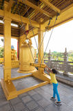 La ragazza suona la campana al tempio buddista Immagine Stock