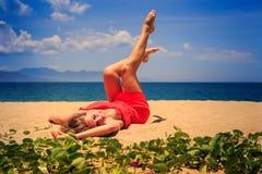la ragazza superiore di vista nelle bugie di rosso sulla sabbia solleva le ginocchia delle curvature delle gambe Immagini Stock