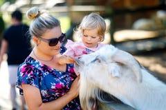 La ragazza sveglia adorabile del bambino e giovane la madre che alimentano le piccole capre e pecore sull'bambini coltivano Belle fotografia stock