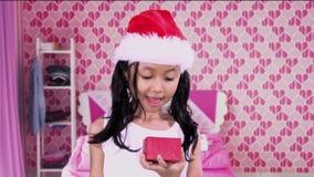 La ragazza sveglia apre il regalo di Natale in camera da letto video d archivio