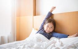 La ragazza sveglia asiatica sveglia ed allungando sul letto Immagini Stock