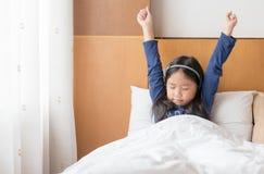 La ragazza sveglia asiatica sveglia ed allungando sul letto nella mattina Fotografia Stock