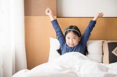 La ragazza sveglia asiatica sveglia ed allungando sulla mattina Fotografie Stock Libere da Diritti
