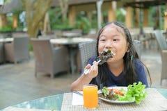 La ragazza sveglia asiatica gode di di mangiare l'insalata vegatable immagine stock