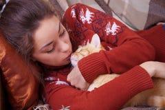 La ragazza sveglia bacia un gatto rosso Fotografie Stock