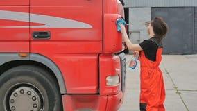 La ragazza sveglia che porta i camici arancio lucida il camion stock footage