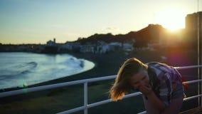 La ragazza sveglia con bei capelli è felice e sorride vicino al mare archivi video