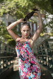 La ragazza sveglia con i capelli ricci porta il vestito floreale Fotografia Stock