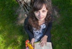 La ragazza sveglia con i fiori ed il libro in città parcheggiano Fotografia Stock Libera da Diritti