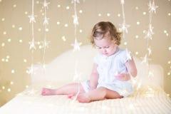 La ragazza sveglia del bambino con il suo giocattolo riguarda un letto bianco fra le belle luci di Natale calde Fotografia Stock Libera da Diritti