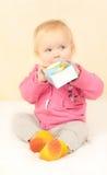 La ragazza sveglia del bambino si siede e spremuta bevente immagini stock libere da diritti