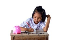 La ragazza sveglia del paese asiatico prende nota delle ricevute e delle monete di reddito con il porcellino salvadanaio isolato  fotografia stock libera da diritti