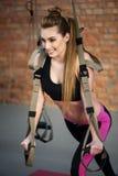 La ragazza sveglia di misura sta facendo l'esercizio con attrezzatura Immagine Stock Libera da Diritti
