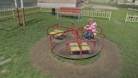La ragazza sveglia divertente sta giocando Bambino femminile gioioso divertendosi sul campo da giuoco archivi video