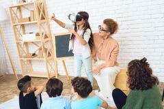 La ragazza sveglia esamina i vetri di realtà virtuale all'aula della scuola elementare Fotografie Stock Libere da Diritti