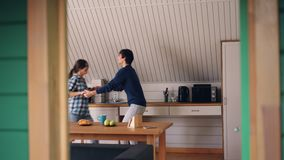 La ragazza sveglia felice dei giovani ed il suo ragazzo allegro stanno ballando nella cucina che abbraccia e che esprime le sensi stock footage