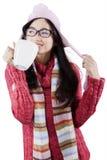 La ragazza sveglia gode della bevanda calda in studio Fotografie Stock