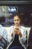La ragazza sveglia guida nel sottopassaggio ed esamina lo schermo dello smartphone fotografia stock